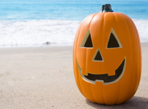 30108182 - halloween pumpkin on the sandy beach by ocean
